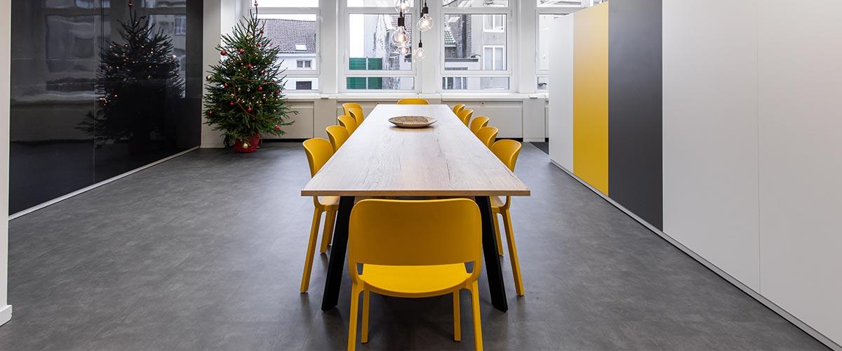 Salle de réfectoire avec deux types de tables et chaises.