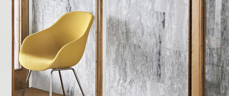 Un mur en béton gris avec une chaise jaune devant qui montre comment bien associer les couleurs.