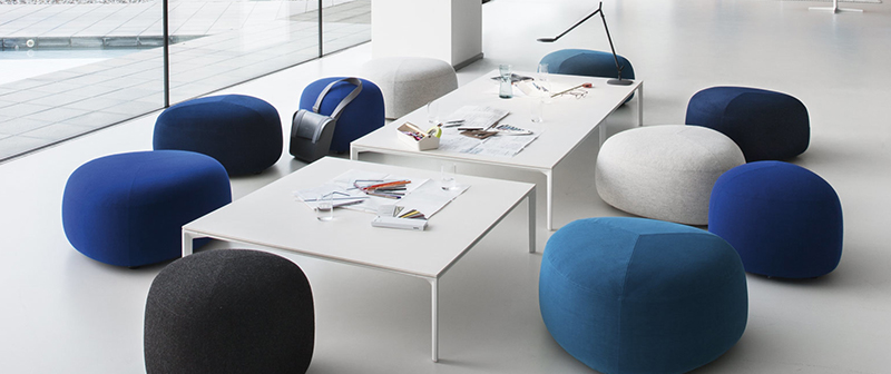 Un pièce blanche aménagée avec des poufs bleus de différentes teintes.