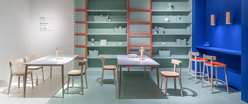 Une pièce aménagée avec des tables et chaises colorées qui montre comment associer les couleurs.
