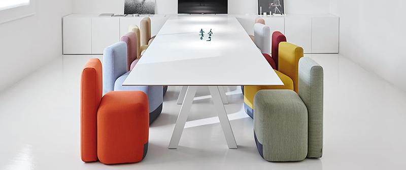 Une pièce blanche avec des chaises colorées autour d'une table.